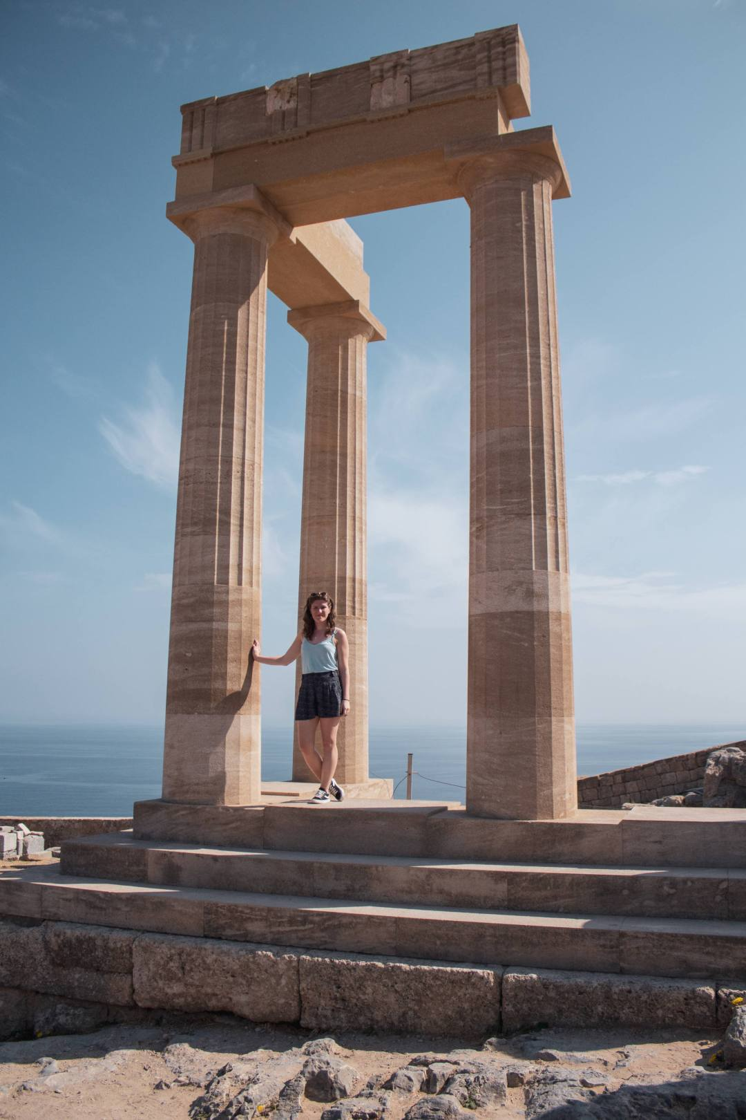 woman stands next to columns on top of lindos acropolis