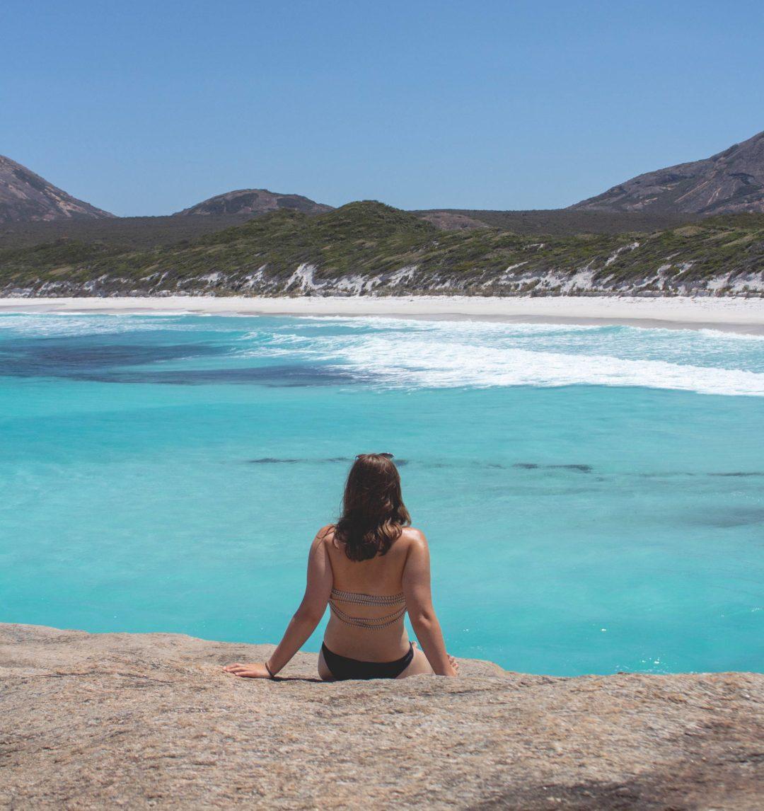 Woman sits on rocks at Hellfire Bay Esperance