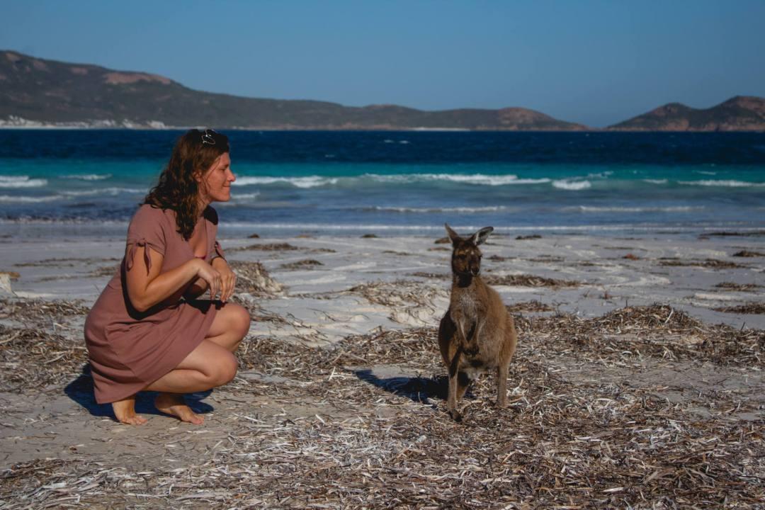woman poses next to kangaroo at Lucky Bay