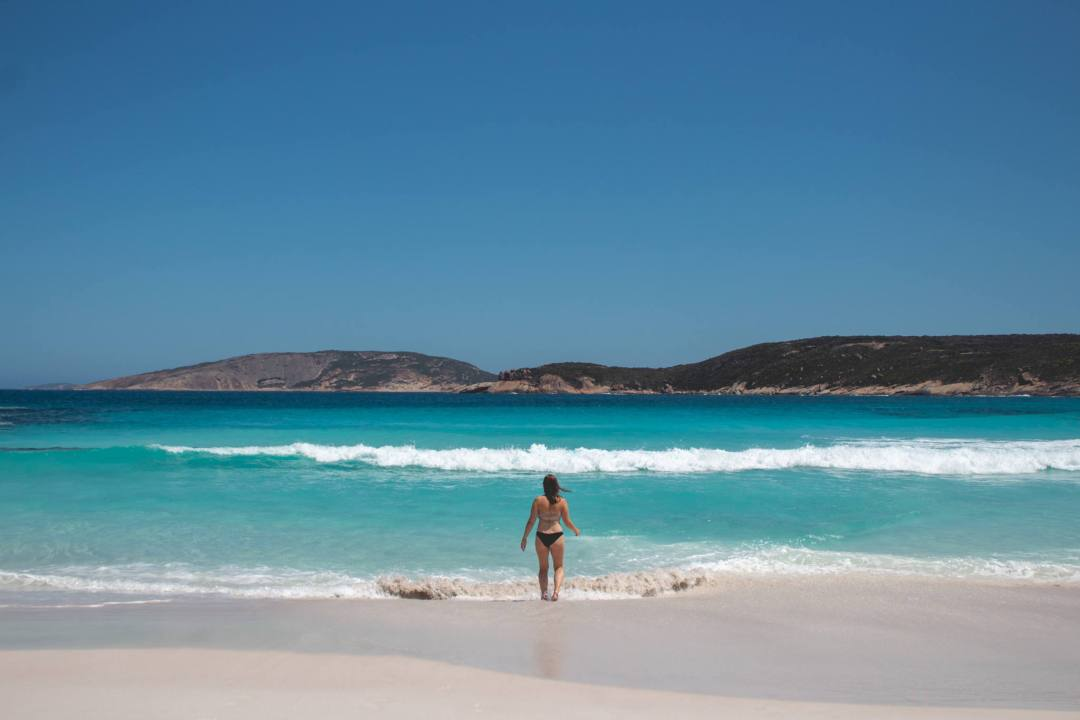 Woman walking into ocean at beach in Esperance