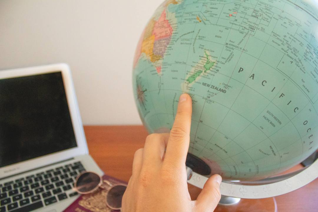 hand points to new zealand on globe