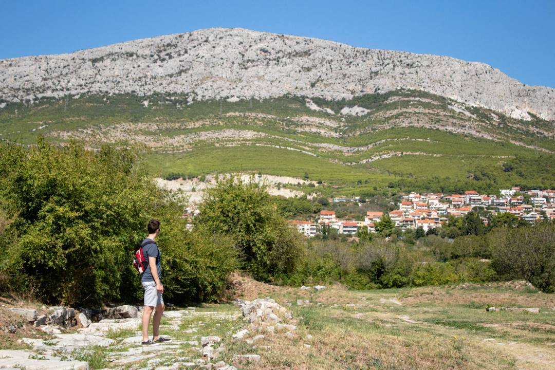 man looks up at hill from roman ruins