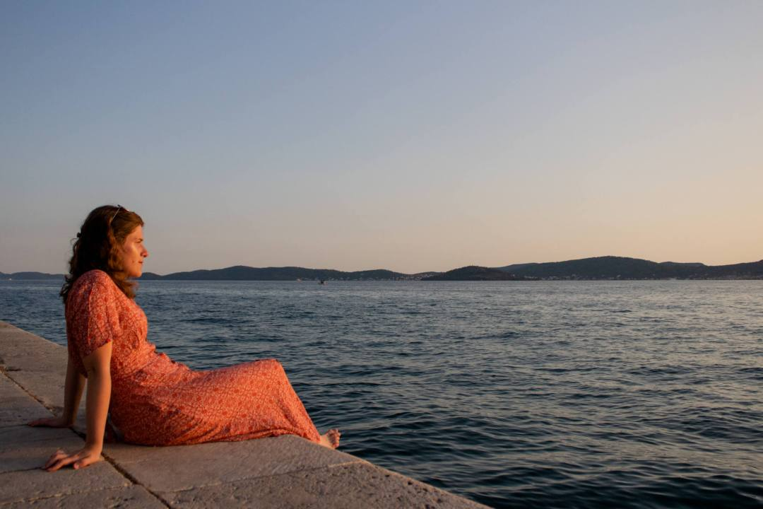 woman looks out across ocean at sunset
