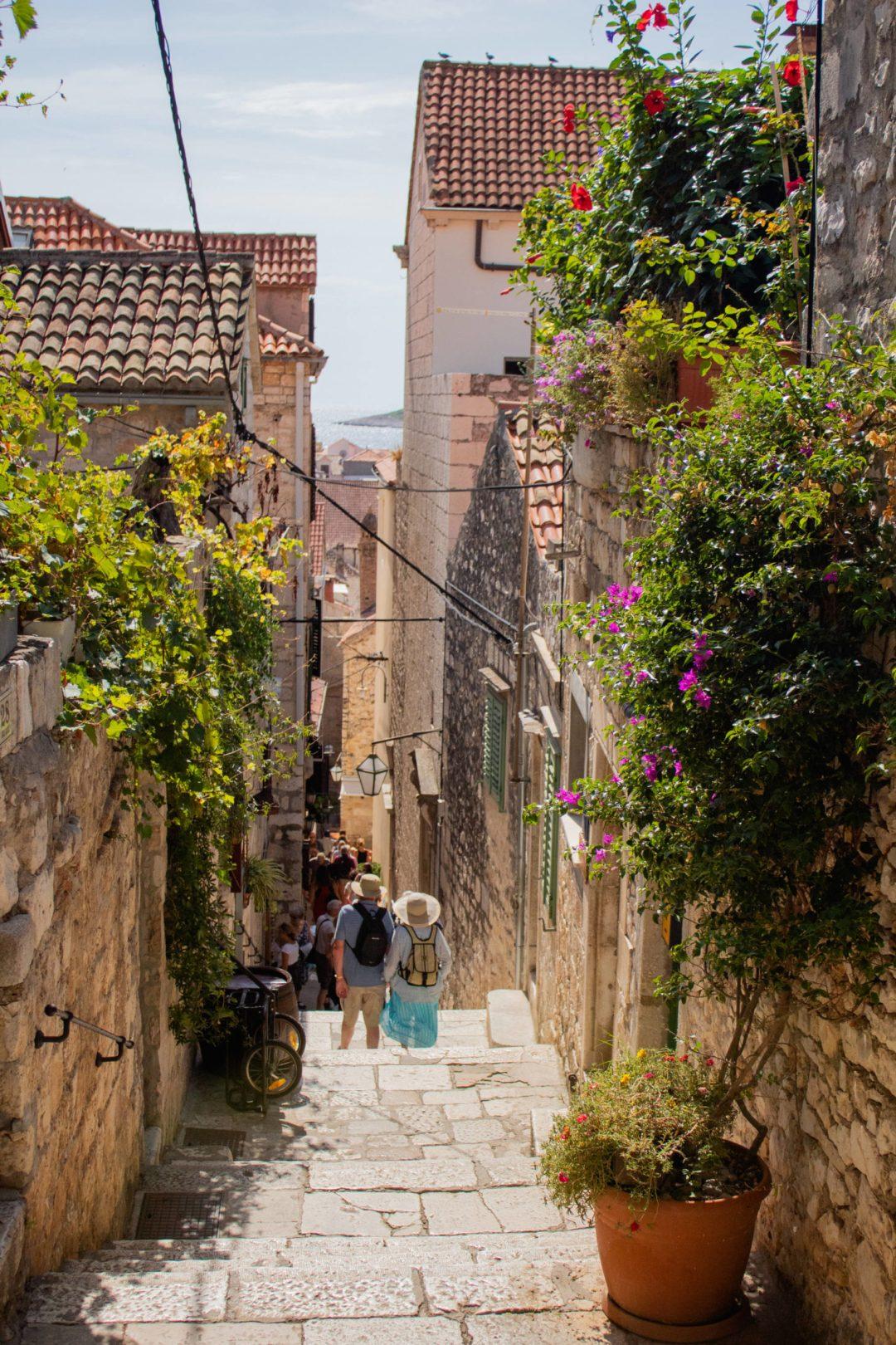 tourists walk down steps in hvar old town