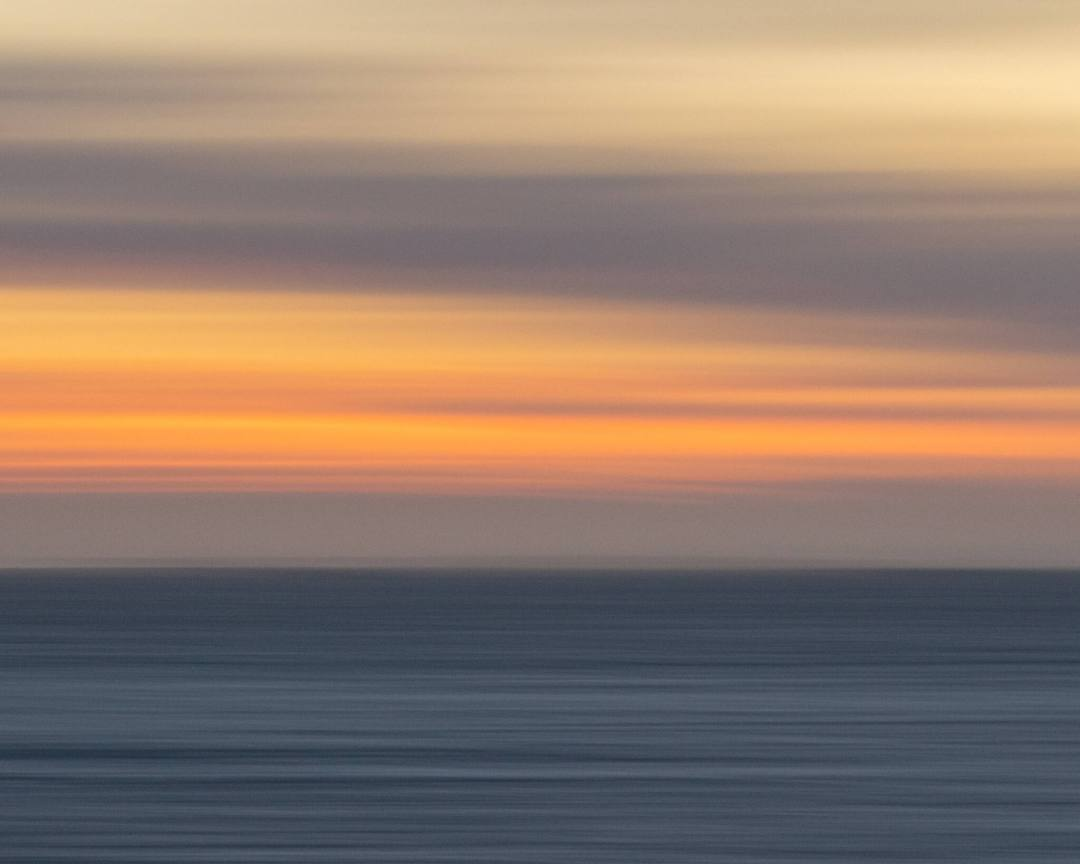 sunset over the ocean with long exposure causes a smooth movement effect