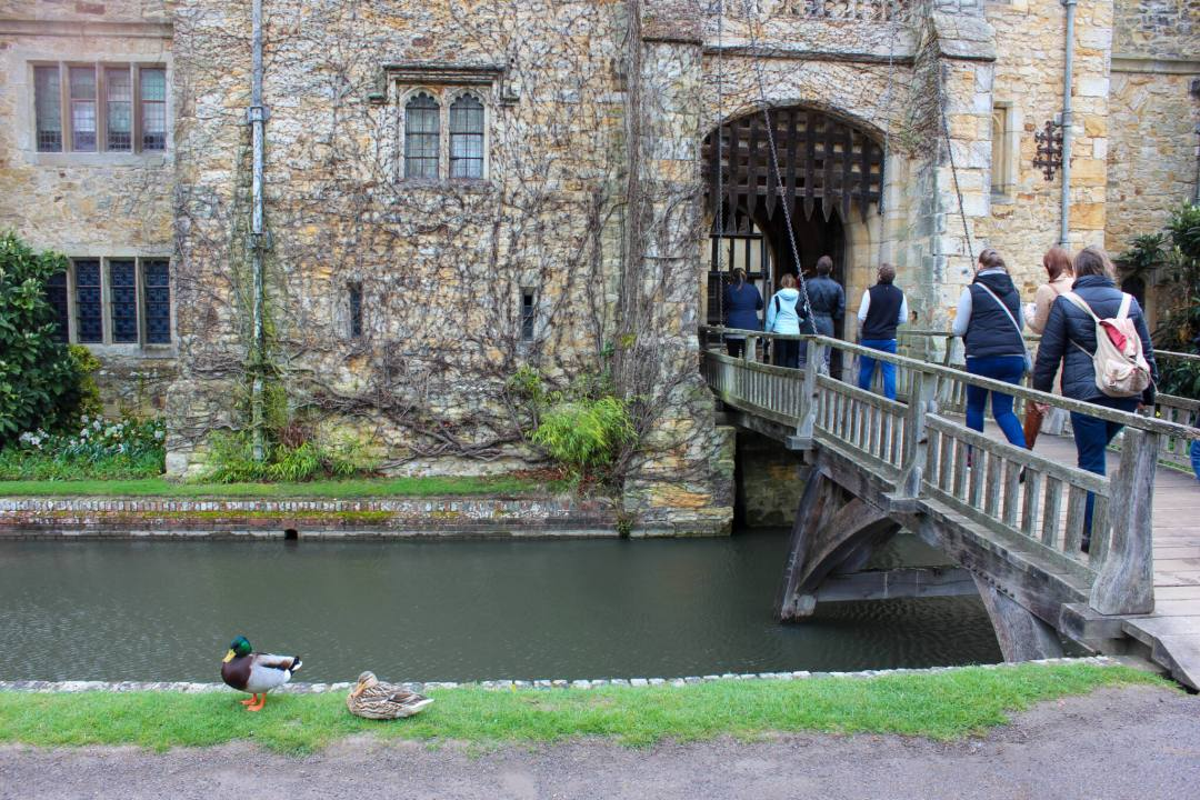 tourists walk across drawbridge over hever bridge moat