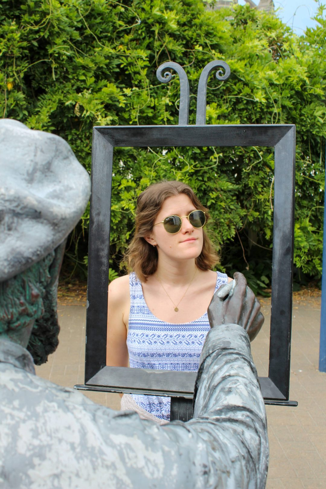 Woman stands in the frame of a sculpture that depicts an artist painting a picture