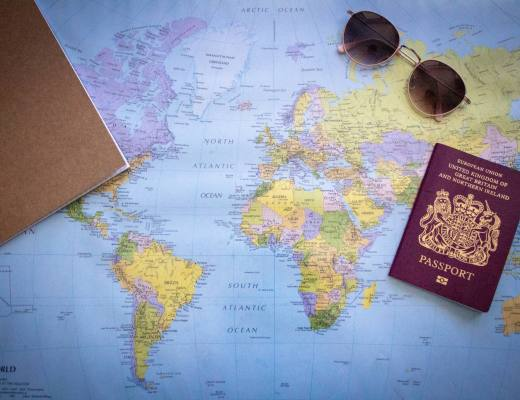 Top-down view of world map with sunglasses notebook and British passport on top