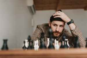 a man in checkered shirt playing chess