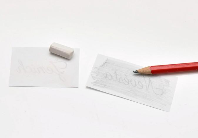 Papírky s texty přetřené křídou a tužkou - bílá křída a tužka