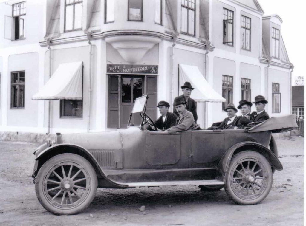 """Stiliga herrar på bilturné i Svegs municipalsamhälle. I bakgrunden Johanssons kafé och konditori i hörnan Kyrkogatan/Herrögatan, senare populär ölstuga med smeknamnet """"Ölan"""" och i annan del av byggnaden en mer restaurangbetonad salong med vita dukar på bordet och uniformsklädda servitriser. L.O. Johanssons fastighet stod klar 1920 medan dennes bostad mitt emot på Herrögatan hade byggts 10 år tidigare, som senare blev Alma Lindskogs hattaffär och bostad där dagens ägare Ann-Marie Mattsson på bottenvåningen driver damfrisörsalongen Die Welle vägg i vägg med dottern Helenas salong Sears & Co. Foto: privat"""