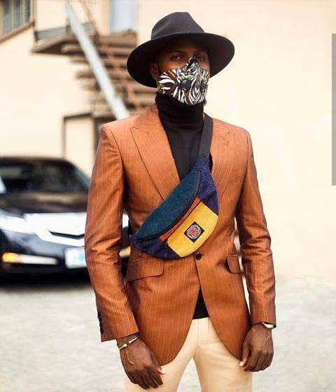 Akin Faminu in brown suit wearing face mask
