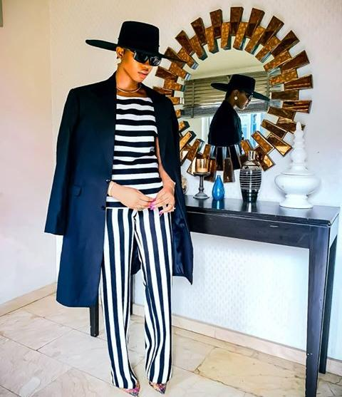 Angel Obasi in black and white striped jump suit and black over coat