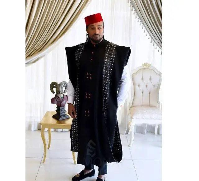 man rocking black agbada with red cap