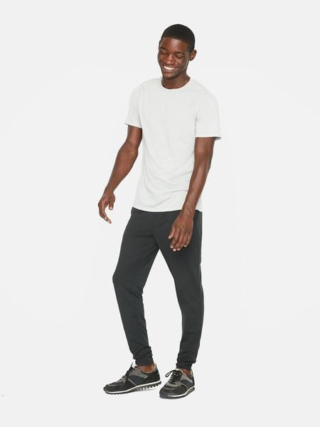 smiling man wearing white t-shirt, black jeans and black sneakers