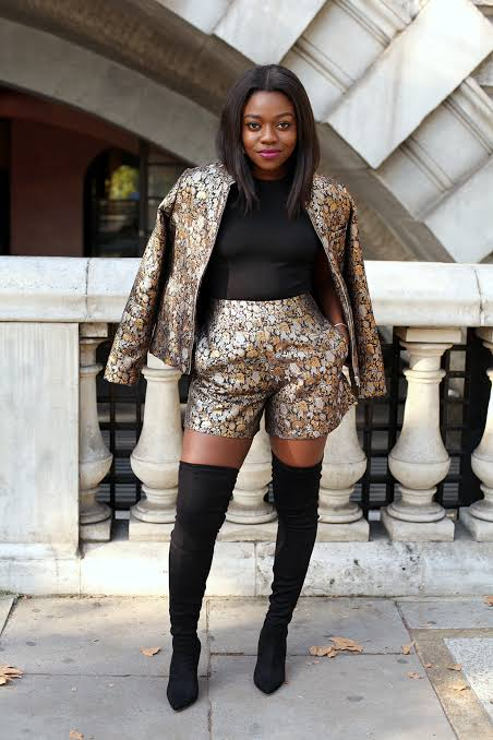 African lady rocking black over-the-knee boots with heels