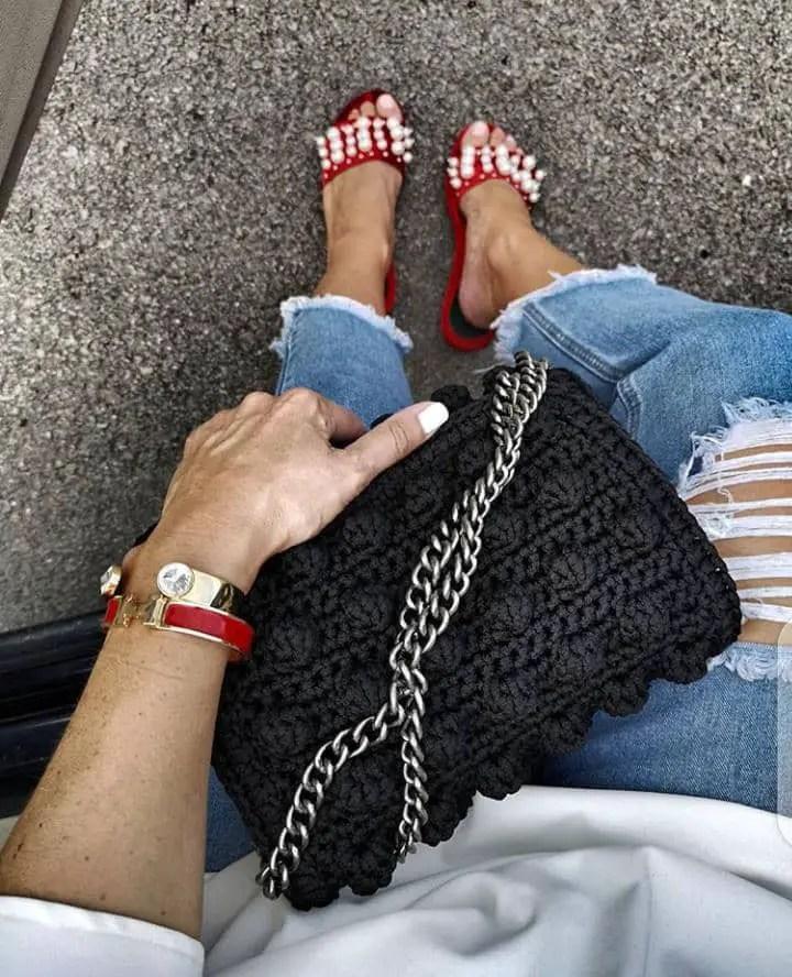 holding a black handbag