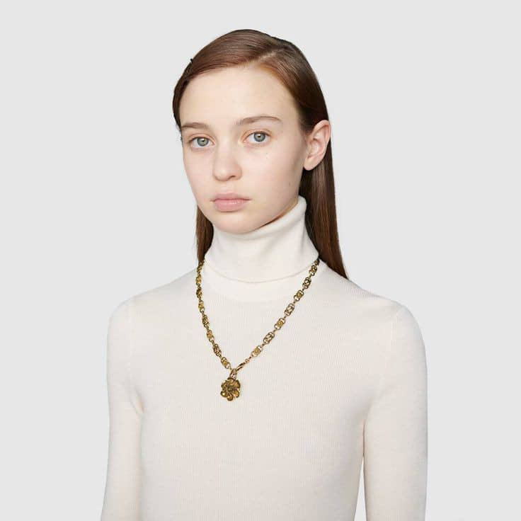 lady in high neckline top with a necklace with pendant