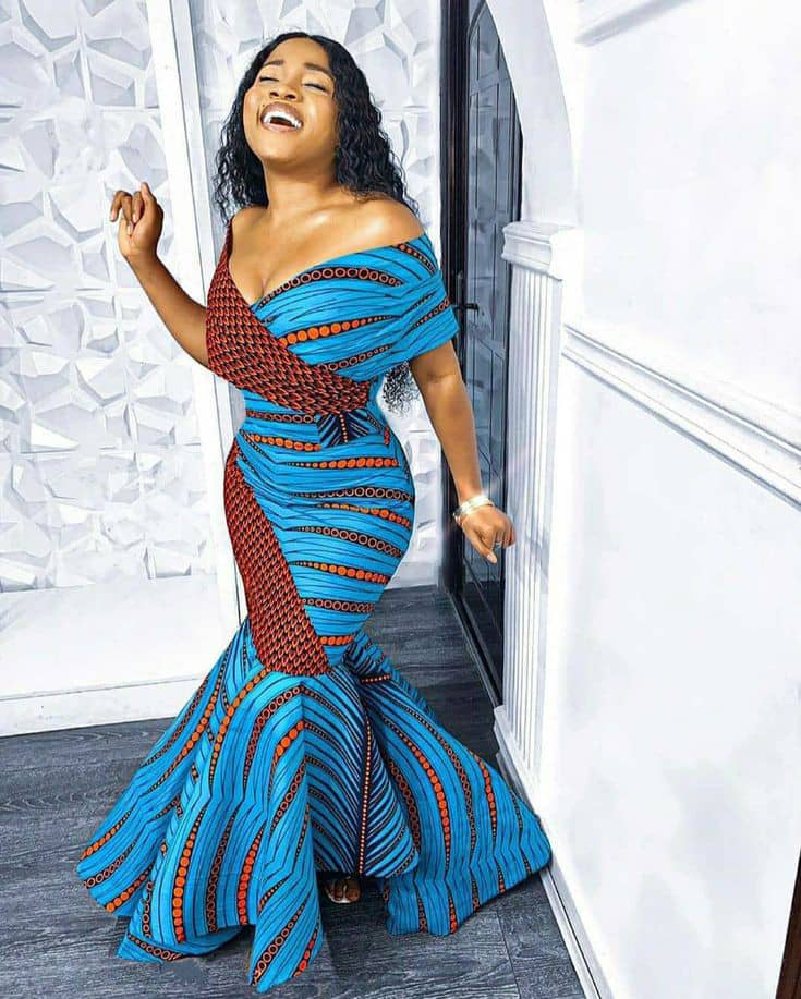 smiling lady in a long ankara dress