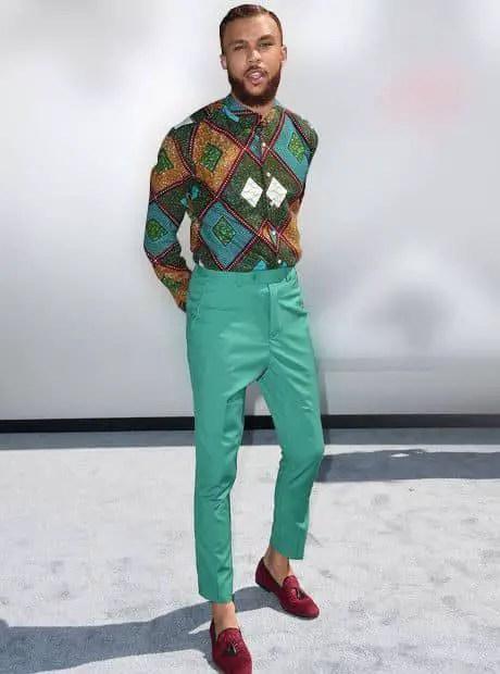 Jidenna wearing long sleeves ankara shirt with plain green trousers