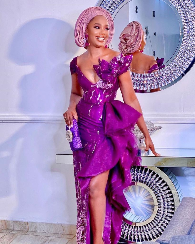 woman in purple aso ebi attire carrying a purple minaudiere