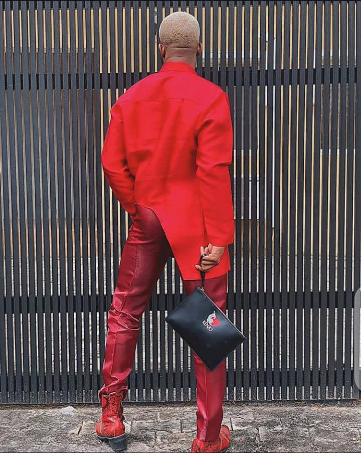 man in red outfit carrying a black purse-bag