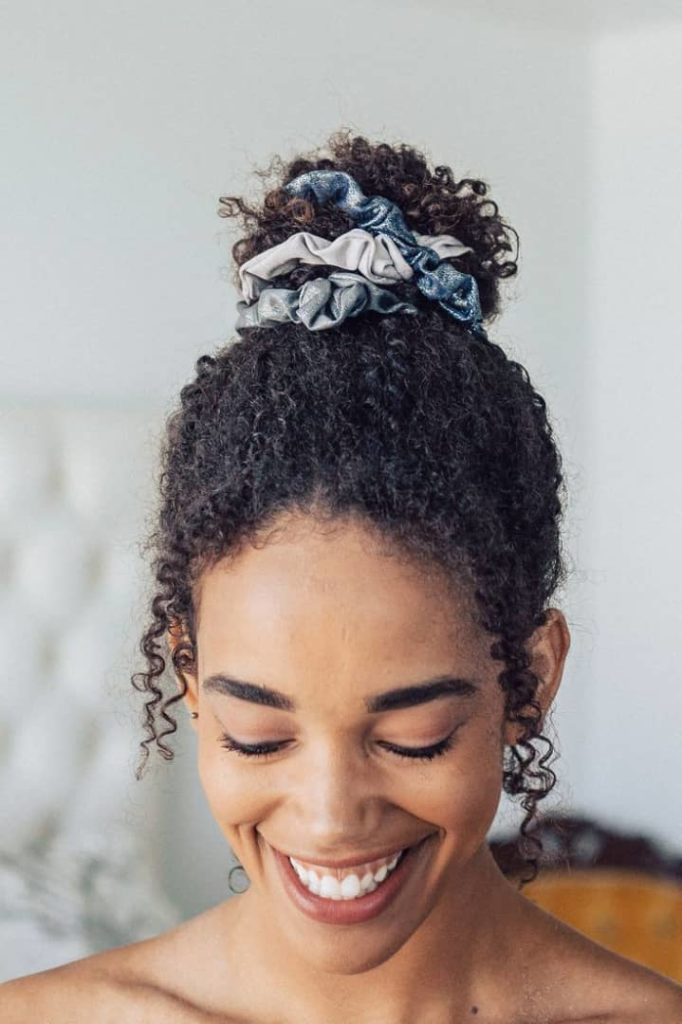 smiling lady wearing scrunchies on her hair