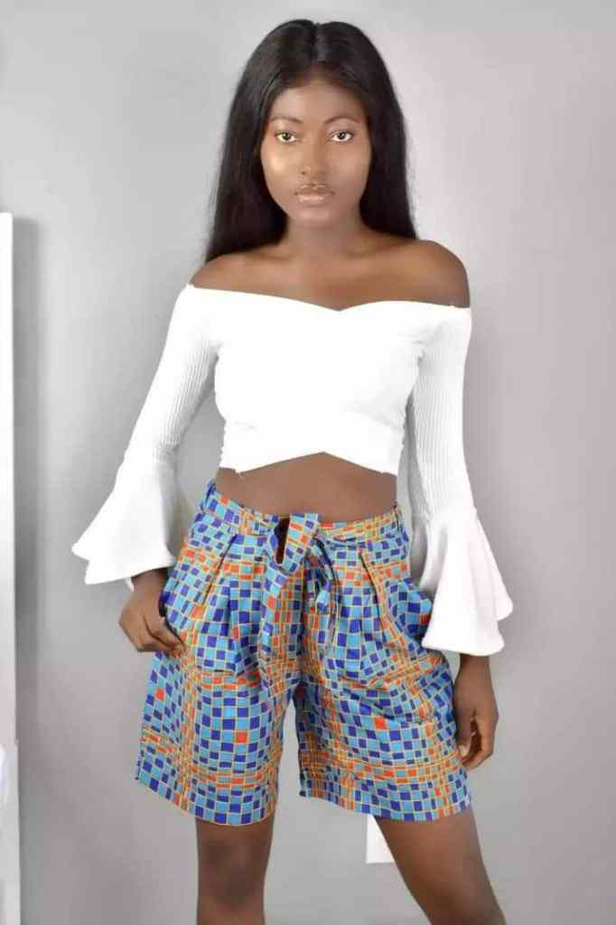 lady wearing ankara shorts with white top