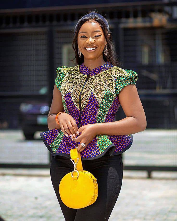 smiling lady wearing ankara sleeveless top with a yellow bag
