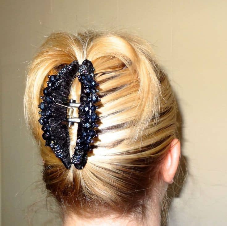 black jaw clip holding a blond hair