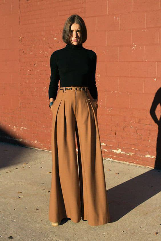 white lady wearing black turtle neck top and brown palazzo pants