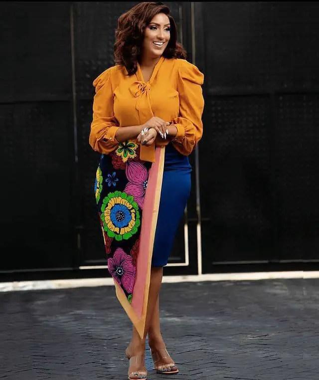 smiling actress wearing a top and ankara skirt