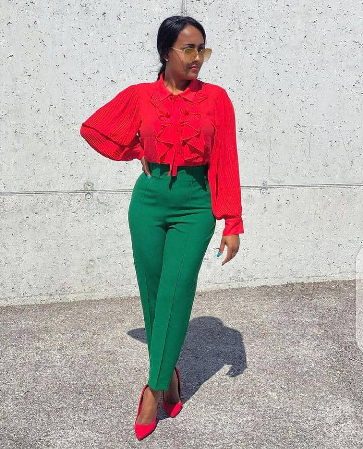 lady in red top and green pants with red shoes