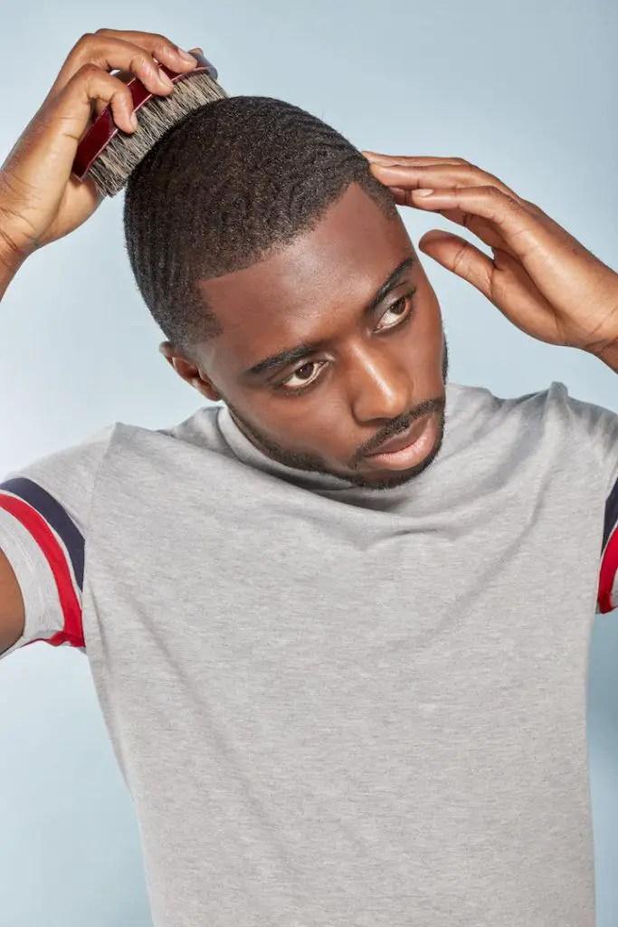 black man combing hair