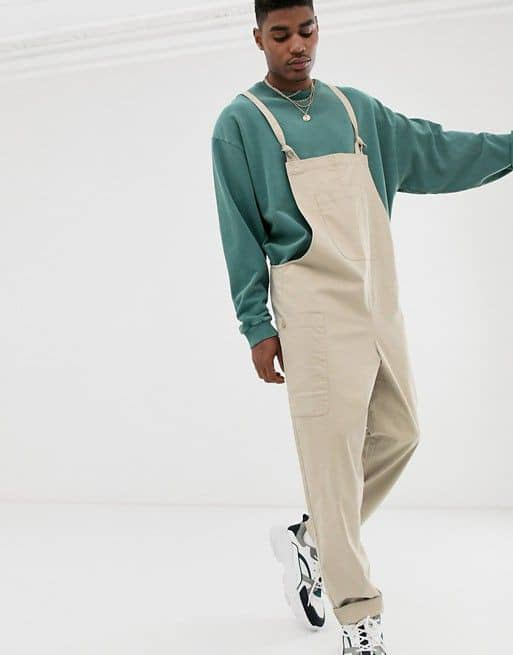 man wearing dungaree with sneakers
