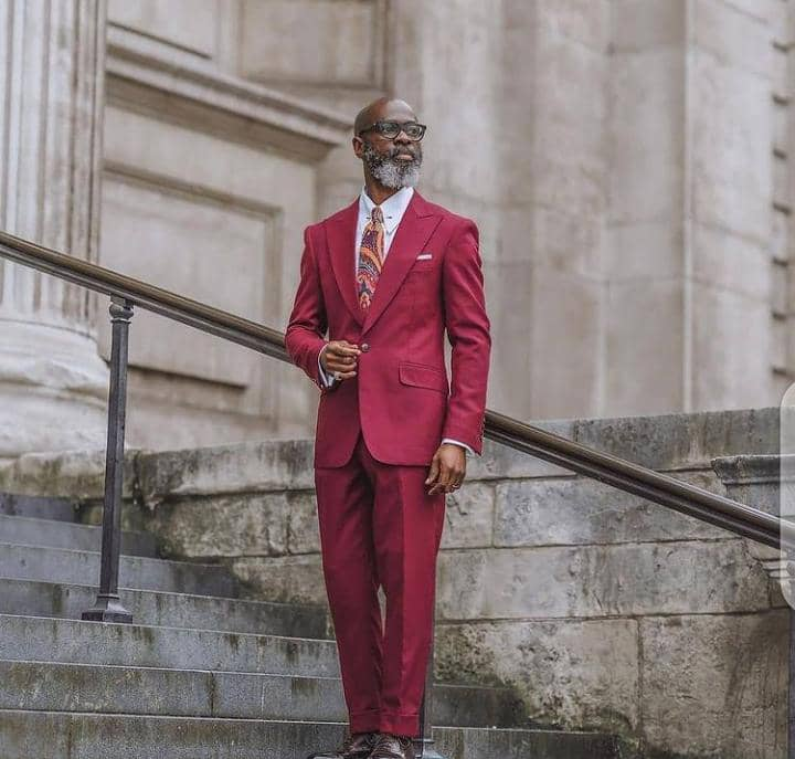old man wearing red suit and tie to work