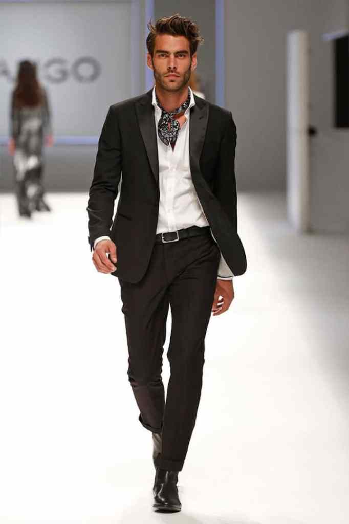 a male model wearing scarf on open-neck suit on the runway