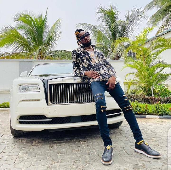 D'banj chilling in casual outfit in front of a white Rolls Royce