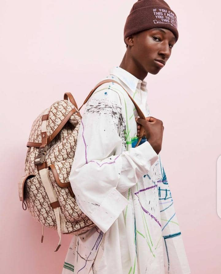 a model wearing Dior outfit with hat and backpack