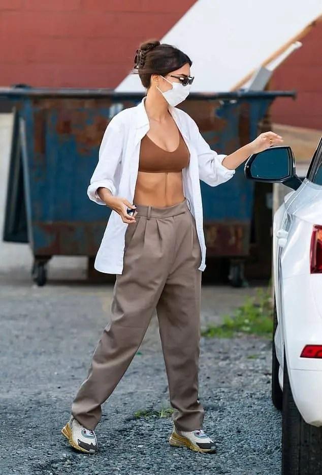 lady layering white shirt on bra top