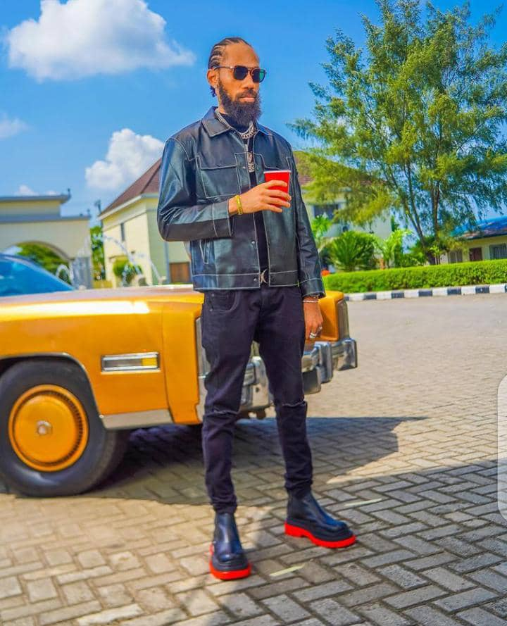 Phyno wearing jeans jacket and jeans pants in front of a car