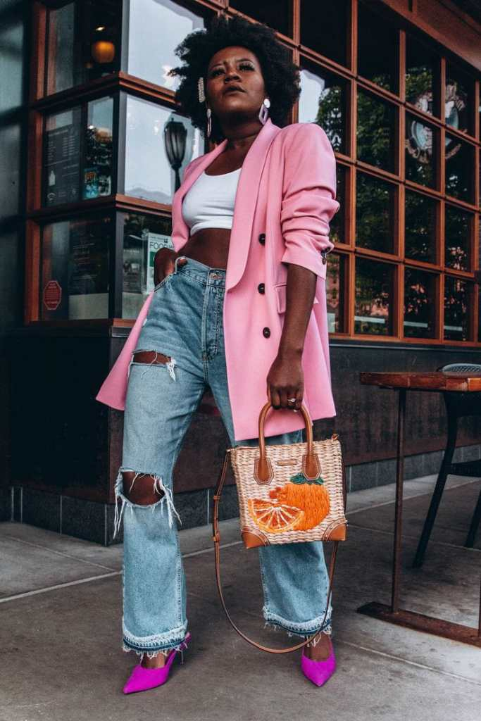 lady wearing pink blazer and jeans with handbag