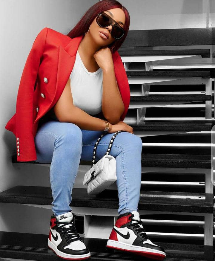 lady in red blazer and jeans wearing sneakers