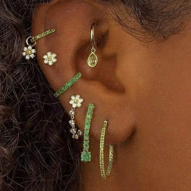 close-up shot of multiple earrings on ear