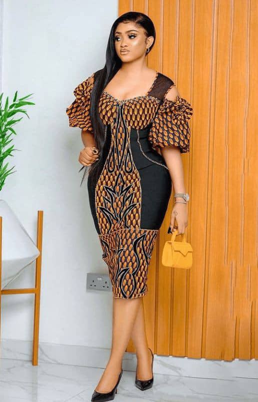 lady wearing ankara dress with a touch of bkack material