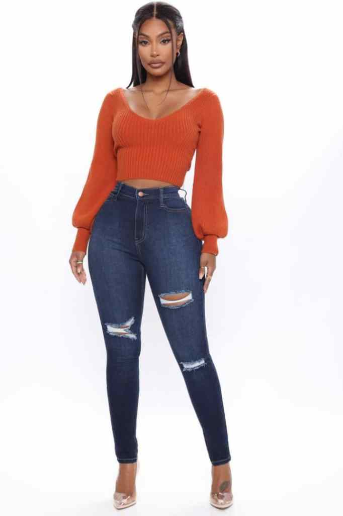 lady wearing orange top and high waist jeans
