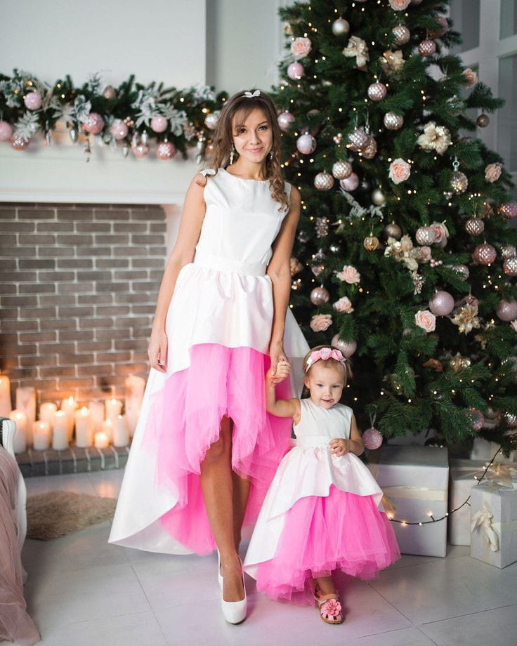 mother and daughter wearing matching dresses in front of the Christmas tree