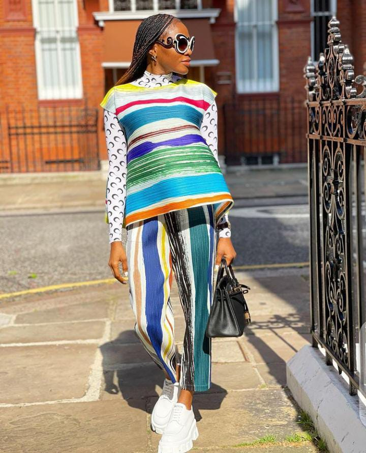 lady wearing multic-color outfit with glasses and sneakers