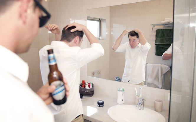 Groomsmen checking hair in mirror
