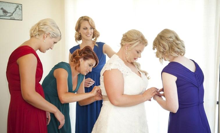 Bride putting on dress